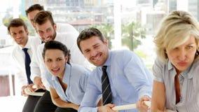 Bedrijfsmensen die een kabel met inspanning trekken stock video