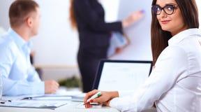 Bedrijfsmensen die en op commerciële vergadering, in bureau zitten bespreken Royalty-vrije Stock Fotografie