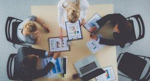 Bedrijfsmensen die en op commerciële vergadering, in bureau zitten bespreken Royalty-vrije Stock Foto's