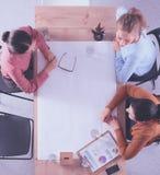Bedrijfsmensen die en op vergadering, in bureau zitten bespreken Stock Afbeelding