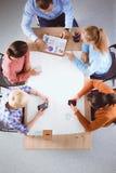 Bedrijfsmensen die en op vergadering, in bureau zitten bespreken Stock Fotografie
