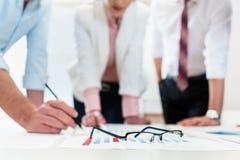 Bedrijfsmensen die gegevens - glazen over grafiek analyseren Stock Afbeeldingen