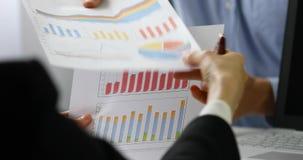 bedrijfsmensen die grafiek en grafiekrapporten bespreken stock videobeelden