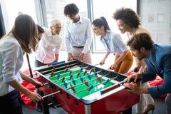 Bedrijfsmensen die grote tijd hebben samen Collega's die lijstvoetbal in bureau spelen royalty-vrije stock fotografie