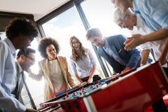 Bedrijfsmensen die grote tijd hebben samen Collega's die lijstvoetbal in bureau spelen royalty-vrije stock foto