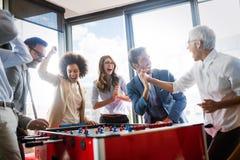 Bedrijfsmensen die grote tijd hebben samen Collega's die lijstvoetbal in modern bureau spelen royalty-vrije stock foto