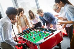 Bedrijfsmensen die grote tijd hebben samen Collega's die lijstvoetbal in modern bureau spelen stock foto