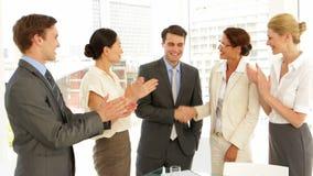 Bedrijfsmensen die handen schudden bij gesprek terwijl anderen slaan stock videobeelden