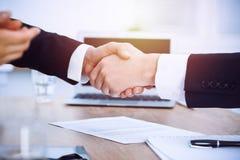 Bedrijfsmensen die handen schudden bij vergadering of onderhandeling in het bureau Handdrukconcept De partners zijn tevreden omda stock afbeelding