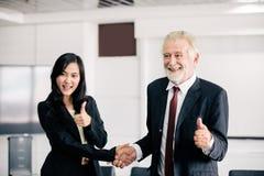 Bedrijfsmensen die handen schudden en hun overeenkomst glimlachen om contract te ondertekenen en omhoog een vergadering be?indige stock afbeelding