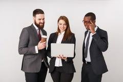 Bedrijfsmensen die laptop en het glimlachen bekijken stock foto