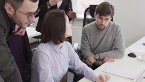Bedrijfsmensen die laptop het scherm tijdens creatieve vergadering op het werk bekijken stock videobeelden