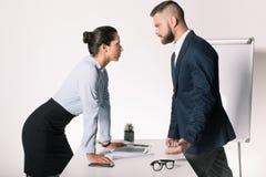 Bedrijfsmensen die meningsverschil hebben en elkaar in bureau bekijken stock afbeeldingen