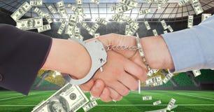 Bedrijfsmensen die met handcuffs handen schudden bij voetbalstadion dat corruptie vertegenwoordigt royalty-vrije stock fotografie