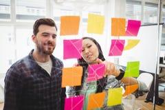 Bedrijfsmensen die multi gekleurde kleverige nota's over glas bekijken Stock Afbeeldingen