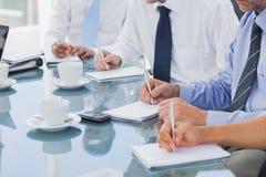 Bedrijfsmensen die nota's over blocnotes nemen Royalty-vrije Stock Afbeelding