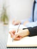 Bedrijfsmensen die nota's schrijven die in het bureau zitten stock foto