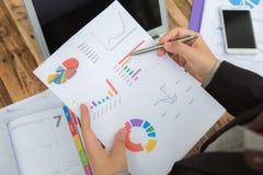 Bedrijfsmensen die op bedrijfsdocument richten tijdens Stock Foto's