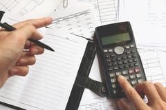 Bedrijfsmensen die op calculatorzitting bij de lijst tellen clo Stock Afbeelding