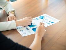 Bedrijfsmensen die op diagrammen richten Stock Afbeeldingen