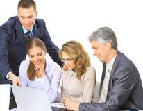 Bedrijfsmensen die op een collectieve vergadering zitten die in laptop werken Stock Afbeeldingen