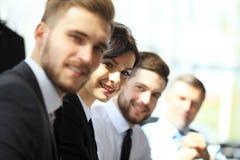 Bedrijfsmensen die op een rij en, nadruk aan jonge vrouw werken zitten Stock Foto's