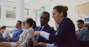 Bedrijfsmensen die over digitale tablet in een seminarie 4k bespreken stock videobeelden