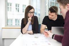 Bedrijfsmensen die over Grafiek bij Bureau bespreken Stock Afbeeldingen