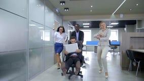 Bedrijfsmensen die pret hebben die hun partners duwen die op bureaustoelen rennen stock video