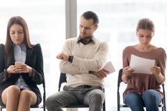 Bedrijfsmensen die in rij zitten die op vergadering wachten om te beginnen royalty-vrije stock foto