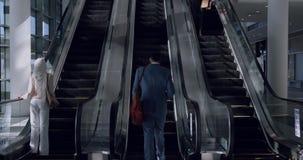 Bedrijfsmensen die roltrap in een modern bureau 4k gebruiken stock video