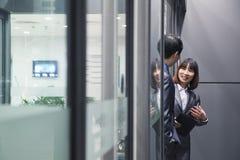 Bedrijfsmensen die samen door een glasmuur spreken Stock Afbeeldingen