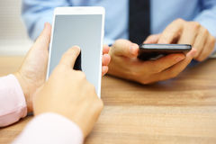 Bedrijfsmensen die slimme mobiele telefoons met behulp van op kantoor royalty-vrije stock afbeeldingen