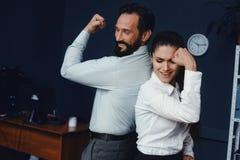 Bedrijfsmensen die spieren in bureau tonen royalty-vrije stock foto