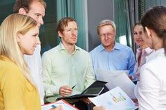 Bedrijfsmensen die teamvergadering hebben in openlucht Stock Afbeelding
