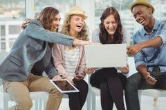 Bedrijfsmensen die terwijl het richten op laptop lachen Stock Foto's