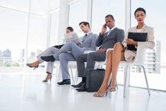 Bedrijfsmensen die terwijl het wachten werken Stock Foto's