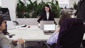 Bedrijfsmensen die tijdens een koffiepauze bij werkplaats in bureau communiceren stock footage