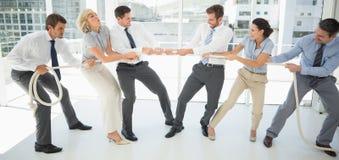 Bedrijfsmensen die touwtrekwedstrijd in bureau spelen Royalty-vrije Stock Foto