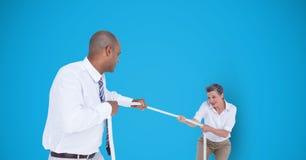 Bedrijfsmensen die touwtrekwedstrijd over blauwe achtergrond spelen Royalty-vrije Stock Foto's