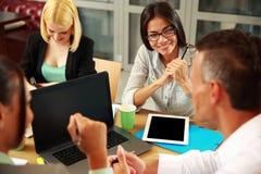 Bedrijfsmensen die vergadering hebben rond lijst Stock Afbeelding