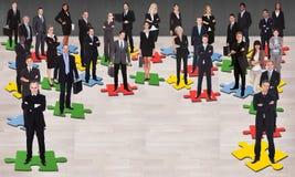 Bedrijfsmensen die zich op figuurzaagstukken bevinden Royalty-vrije Stock Afbeeldingen