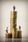 Bedrijfsmensen en euro muntstukstapels Stock Afbeeldingen