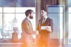 Bedrijfsmensen in grijze coworking bureauzaal royalty-vrije stock afbeelding