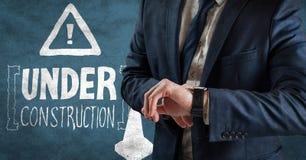 Bedrijfsmensen medio sectie die horloge tegen blauwe achtergrond met witte bouwkrabbel bekijken en Stock Fotografie