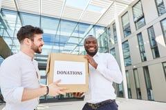Bedrijfsmensen met een karton als schenking in soort stock foto's