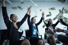 Bedrijfsmensen met opgeheven wapens het werpen van geld in de lucht Stock Fotografie
