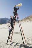 Bedrijfsmensen op Trapladder die Megafoon in Woestijn met behulp van stock foto