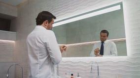 Bedrijfsmensen plaatsende band in luxebadkamers Gelukkige mens die stropdas binnenshuis dragen stock videobeelden