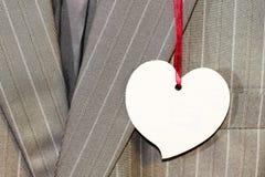 Bedrijfsmensen` s grijs kostuum met een prijskaartje in de vorm van een hart Royalty-vrije Stock Afbeelding